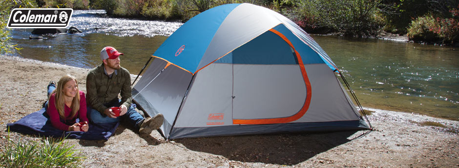Coleman camping gear - an adult couple sitting on a blue blanket near their coleman tent on a river bank in the outdoors