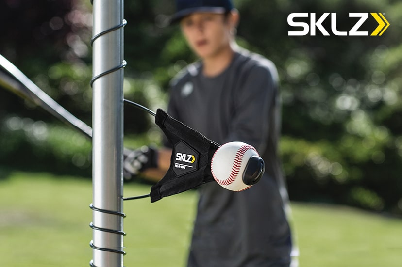Baseball Sklz - Teen hits ball with baseball bat and another prepares to hit a Sklz ball